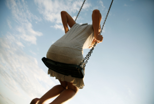 Young woman on swing, rear view, low angle view